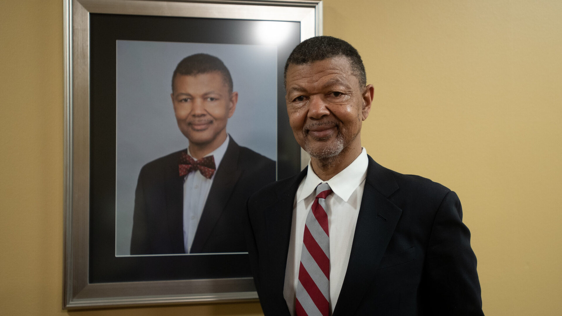Gary Bledsoe '76 standing next to his portrait.