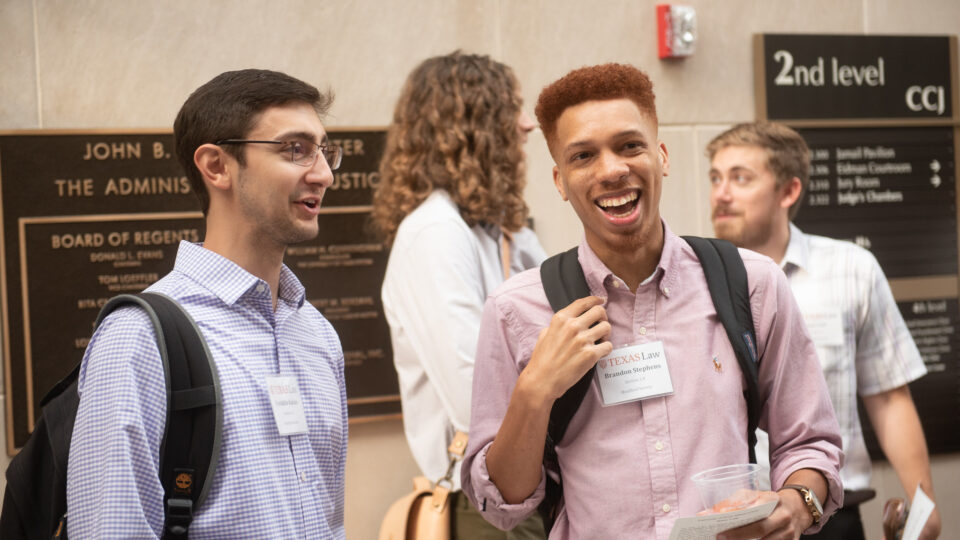 Two students smile and talk at orientation event. Click to make gift online to Texas Law.