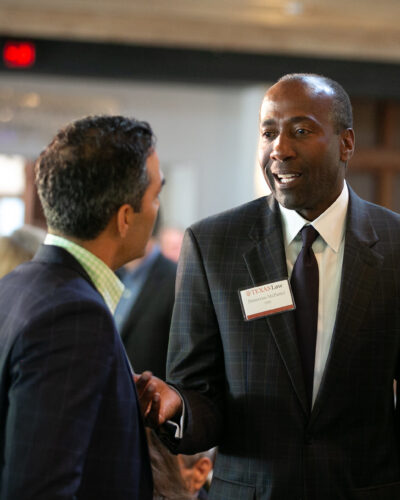 Man in a business suit speaks with others at a networking event