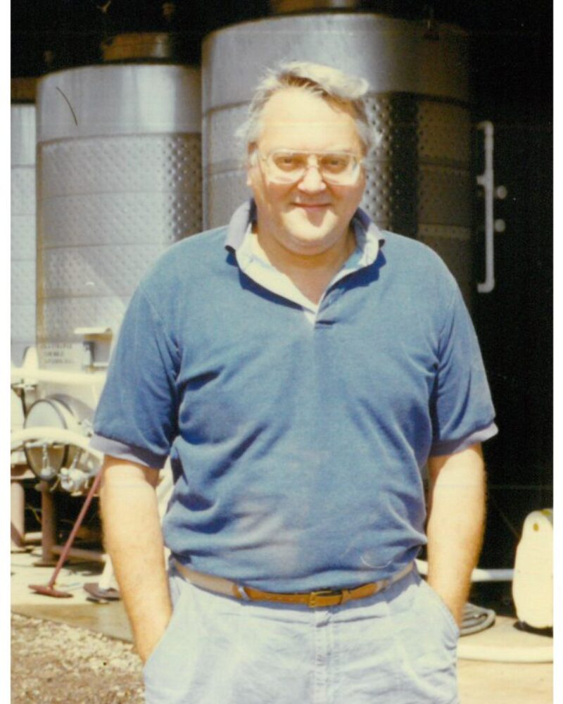 Portrait of Charlie Meeker standing in front of wine barrels during harvest of 1968.