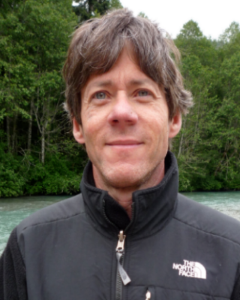 Headshot of Gil Reavis in a black jacket in front of a water/forest scenery