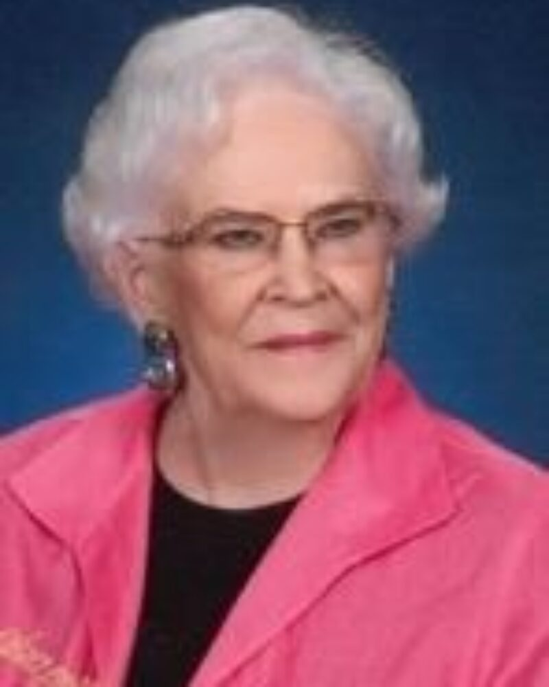 Leona Franklin, wearing a pink jacket in front of a blue background.
