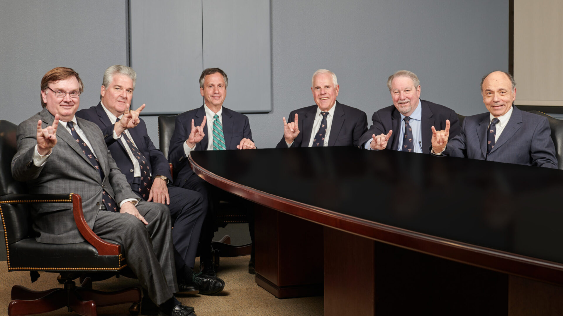 Six men in suits sitting at table