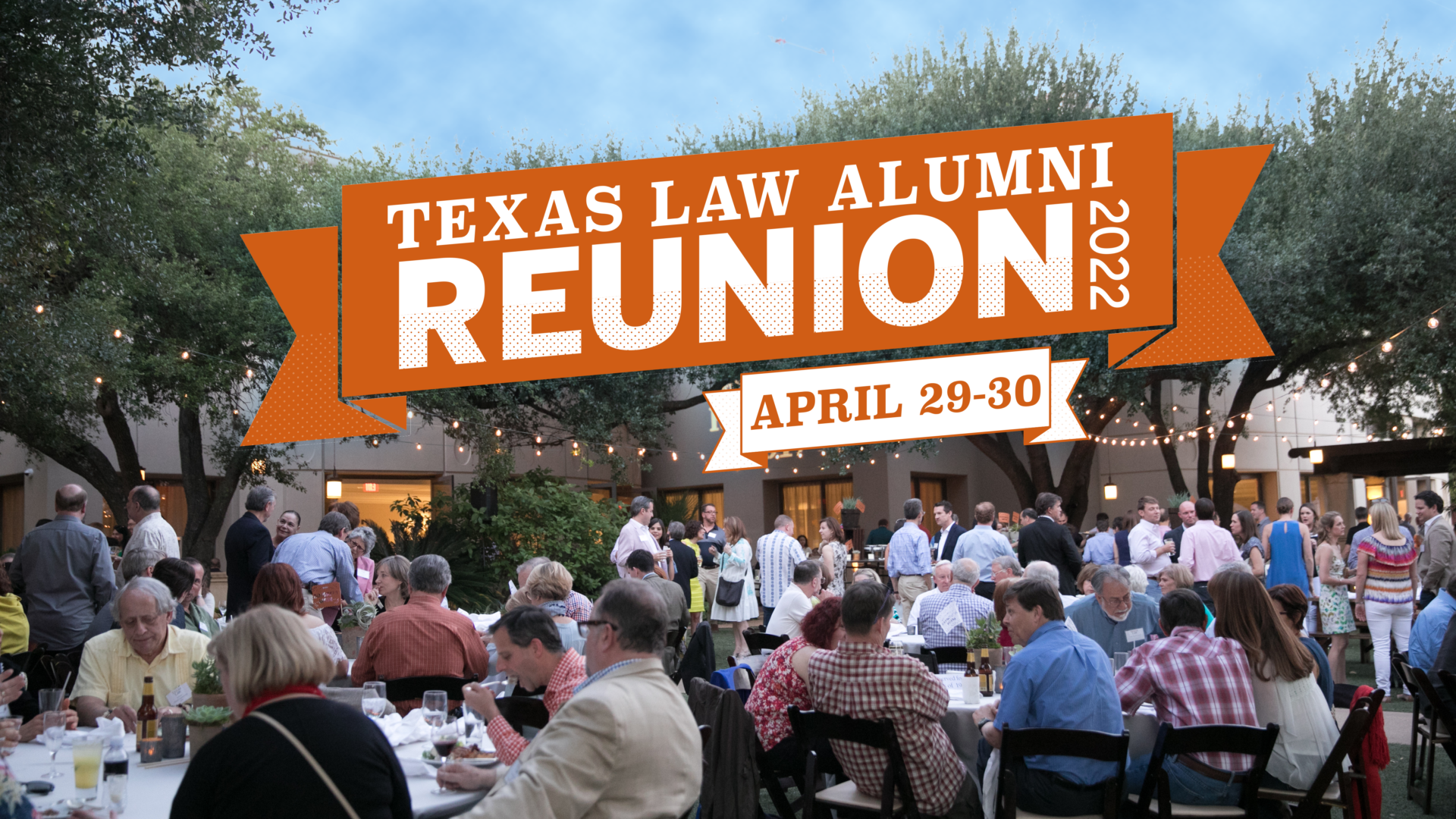 Gathering of alumni outside law school at reunion. Banner above says Texas Law Alumni Reunion 2022. April 29-30