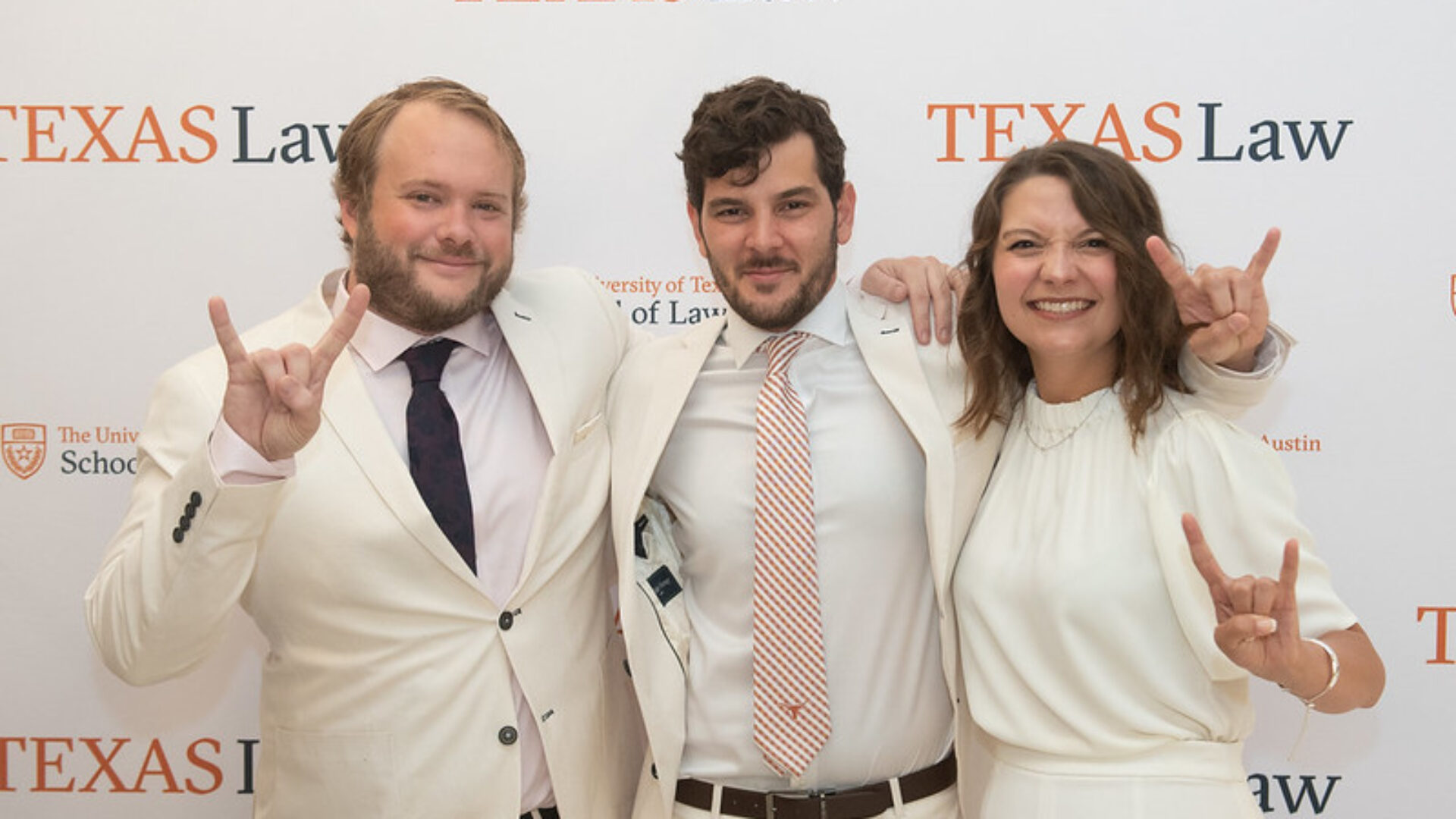 Three graduates wearing white suites in front of a Texas Law banner at the 2021 Sunflower Ceremony