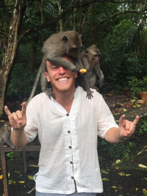student with monkeys on his head